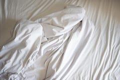 Ungemachte Bettlaken der Falte und weiße Decke im Schlafzimmer nach Schlaf auf geknittertem Gewebe der Draufsicht lizenzfreies stockfoto