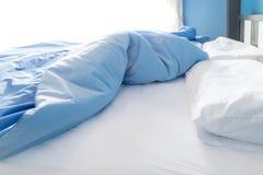 Ungemachtes Bett mit weißem Kissen Stockbild