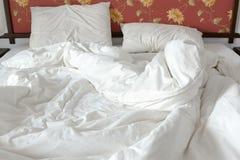 Ungemachtes/unordentliches Bett mit einem Weiß zerknitterte Decke und zwei unordentliche Kissen in einem Bettraum Lizenzfreie Stockfotos