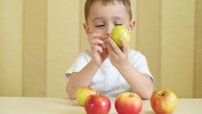 Ungen äter och spelar med röda och gröna äpplen som sitter på tabellen och visar tummen av nöje stock video