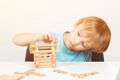 Ungen bygger det lilla trähuset Eco hus guld för begreppskonstruktionsfingrar houses tangenter Pyslekar med kvarter Barndom och u arkivbild