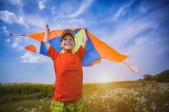 Ungen flyger en drake in i den blåa himlen Royaltyfria Bilder