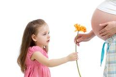 Ungen ger blomman till den gravida modern Arkivfoto