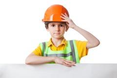 Ungen i arbetskläder står med affischtavlan Arkivfoto