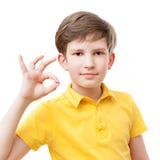 Ungen i gul t-skjorta visar en gest av oken Royaltyfri Foto