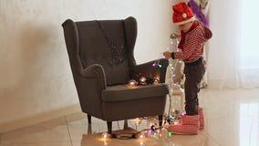 Ungen i Santa Claus beklär att desintegrera brinnande girlander på en stol som bakgrund är kan det använda julillustrationtemat lager videofilmer