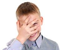 Ungen kikar till och med hans fingrar Arkivbilder