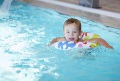 Ungen lär att simma genom att använda en plast- vattencirkel Arkivfoton