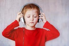 Ungen lyssnar musik hemma Barn med hörlurar arkivbilder