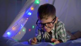 Ungen med en mobiltelefon i glasögon ligger i en vigvam som dekoreras med hemmastadd närbild för girland lager videofilmer