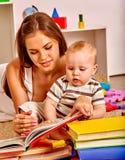 Ungen med modern behandla som ett barn pojken som ligger på golv och, läste boken Royaltyfri Bild