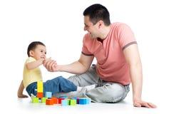 Ungen och hans fader spelar med byggnadskvarter Fotografering för Bildbyråer