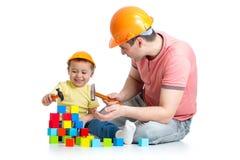 Ungen och hans fader spelar med byggnadskvarter Royaltyfri Fotografi