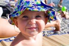 Ungen på stranden i den blåa hatten ler Arkivfoto