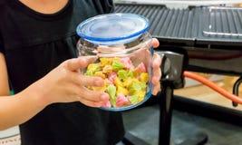 Ungen räcker den hållande glass behållaren med Aalaw eller Alua Arkivbild
