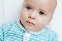 Ungen ser härliga ögon på en ljus bakgrund Arkivfoto