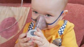 Ungen själv som rymmer en maskering från en inhalator och, andas den hemmastadda medicinen Behandlar inflammation av flygbolagen  arkivfilmer