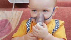 Ungen själv som rymmer en maskering från en inhalator och, andas den hemmastadda medicinen Behandlar inflammation av flygbolagen  stock video