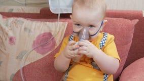 Ungen själv som rymmer en maskering från en inhalator och, andas den hemmastadda medicinen Behandlar inflammation av flygbolagen  lager videofilmer