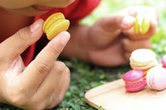 Ungen som äter franska makron, är läcker Royaltyfri Fotografi