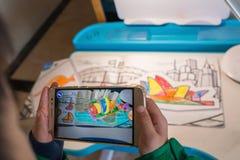 Ungen som spelar ökade popup målningar för verklighet av en färg, fyllde Sydney Opera House via mobil Ar royaltyfri bild