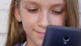 Ungen som spelar minnestavlan, barn använder Smartphone, flickaläsningmeddelanden på internet arkivfilmer