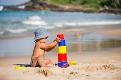 Ungen spelar med leksaker på kusten i sommartid royaltyfria bilder