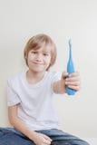 Ungen ställer ut hans elektriska tandborste Royaltyfri Foto