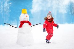 Ungen under promenad i en snöig vinter parkerar Arkivfoton