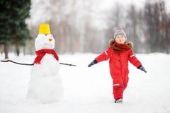 Ungen under promenad i en snöig vinter parkerar Royaltyfria Bilder