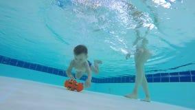 Ungens moder hjälper honom att få en leksak från botten av simbassängen stock video