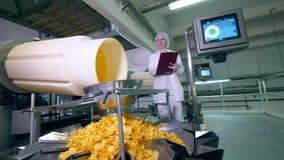 Ungepackte Chips werden unter Steuerung einer Arbeitnehmerin transportiert stock footage