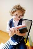 Ungepflegter kleiner Schüler, der einen Stapel Lehrbücher und Lächeln hält stockbilder