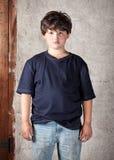 Ungepflegter und schmutziger kaukasischer Junge in den Jeans und in blauem T-Shirt, die vor Stuck-Wand stehen Stockfoto