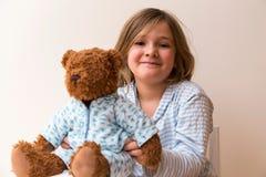 Ungepflegtes kleines Mädchen, das ihren Pyjama-gekleideten Teddybären hält lizenzfreie stockfotografie
