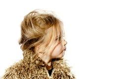 Ungepflegtes Vorschülermädchen mit dem langen Haar kleidete im Pelzmantel an Stockfoto