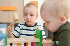 Ungepojkar som spelar med leksaken, blockerar hemma eller dagiset Arkivbild