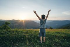 Ungepojken lyftte hans händer upp mot bakgrunden av mountaen Arkivfoto