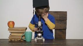 Ungepojken ser i mikroskop Wunderkindbegrepp - smart liten pojke, forskarebarn som arbetar med mikroskopet, b stock video