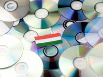 Ungersk flagga överst av CD- och DVD-högen som isoleras på vit Royaltyfri Bild