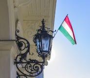Ungersk flagga som hänger på byggnaden och den falska streetlighten Arkivfoto