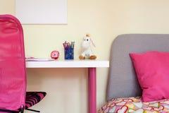 Ungerum med studieskrivbordet och säng Arkivbilder