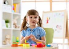 Unges kreativitet barnlera sculpts Den lyckliga lilla flickan gjuter från plasticine på tabellen arkivbild