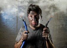 Ungeschulter Mann, der das elektrische Kabel erleidet elektrischen Unfall mit schmutzigem gebranntem Gesicht im lustigen Schockau Lizenzfreie Stockbilder