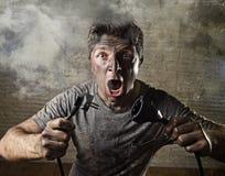 Ungeschultes Mannkabel, das elektrischen Unfall mit schmutzigem gebranntem Gesicht im lustigen Schockausdruck erleidet Stockbild