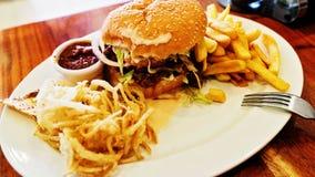 Ungesunde Mahlzeit mit mexikanischem Nacho bricht, der Rindfleischburger ab, geladen mit Käse, Fischrogen, Zwiebelringe Stockfotos