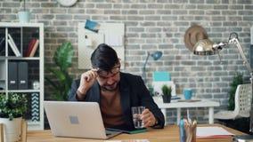 Ungesunder Kerlangestellter, der die Nase dann Trinkwasser im Büro abwischend niest stock video