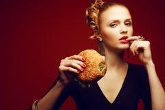 Ungesundes Essen Frittiertes Huhn- oder Fischburgersandwich mit Kopfsalat, Tomate, Käse und Gurke auf hölzernem Hintergrund Frau, stockbild