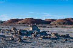 Ungewöhnliche Felsformationen in einer Wüstenlandschaft mit einem Hintergrund von orange und roten Hügeln in Bisti-Ödländern im N lizenzfreies stockfoto