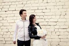 Ungewöhnliche Hochzeitspaare nahe einer Backsteinmauer Stockfotos